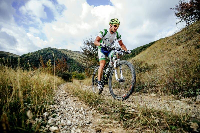 乘坐上升在山和云彩背景的男性车手骑自行车者  免版税图库摄影