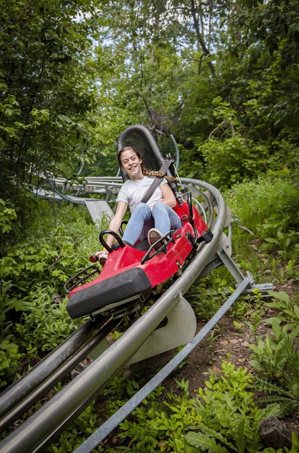 乘坐下坡在一室外过山车好久的微笑的青少年的女孩在一个温暖的夏日 免版税图库摄影