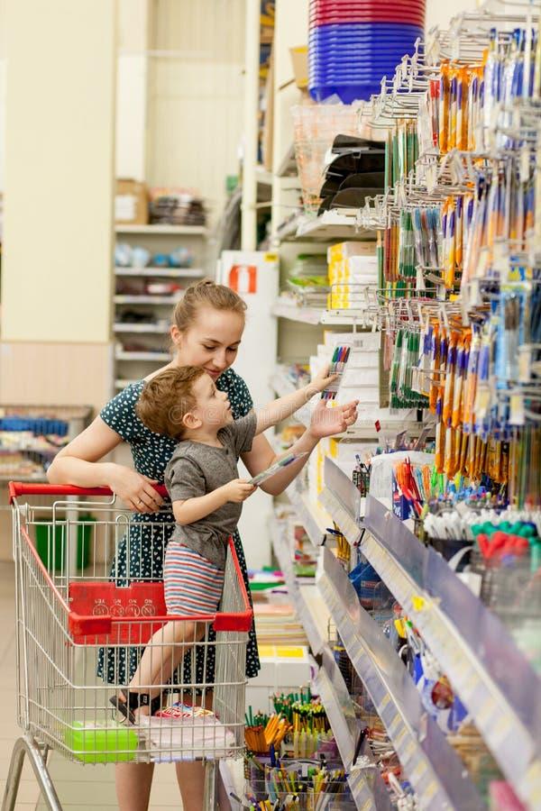 乘坐他们的购物的台车的基辅,乌克兰2019 5月15日,母亲孩子在学校文具商店 小学和 免版税库存照片