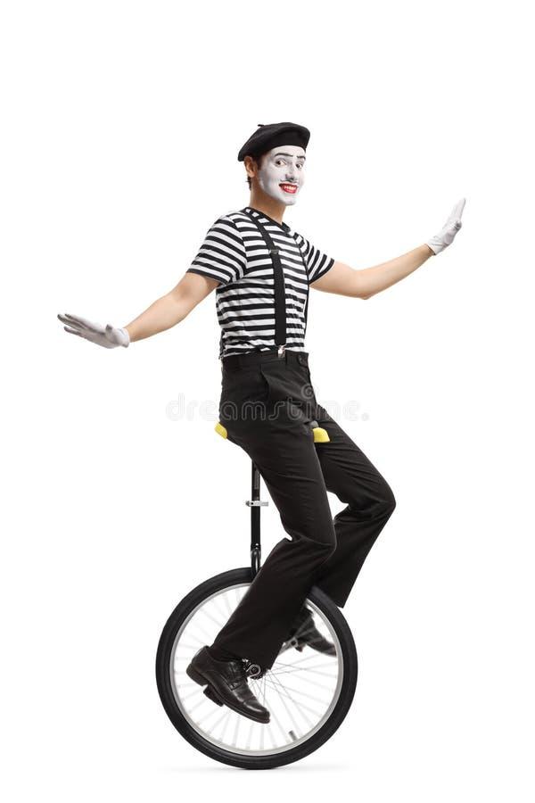 乘坐单轮脚踏车和做鬼脸的笑剧 库存照片
