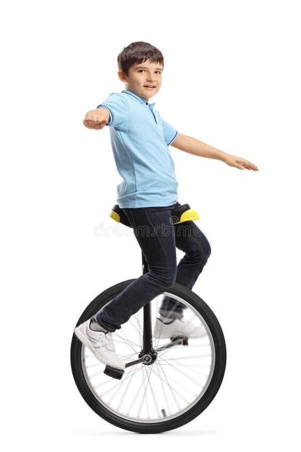 乘坐单轮脚踏车和看照相机的男孩 免版税图库摄影