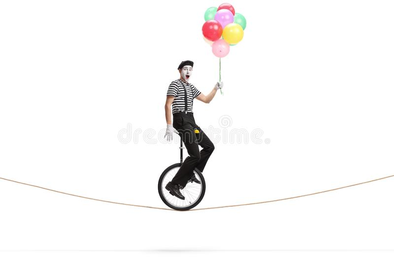 乘坐单轮脚踏车在绳索和拿着一束五颜六色的气球的手势人 免版税图库摄影
