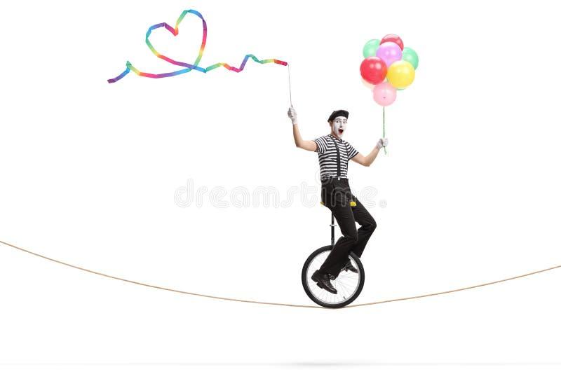 乘坐单轮脚踏车的笑剧在拿着与心形和一束的绳索一条丝带五颜六色的气球 免版税库存图片