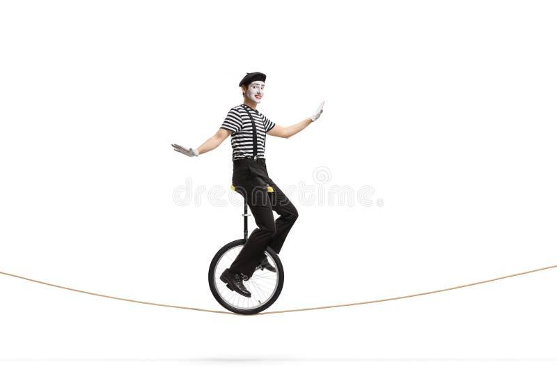 乘坐单轮脚踏车的笑剧在绳索 库存图片