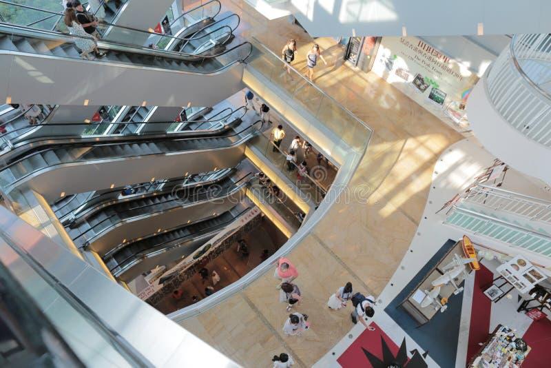 乘坐在一个繁忙的高峰购物中心的自动扶梯的人们在香港 库存照片