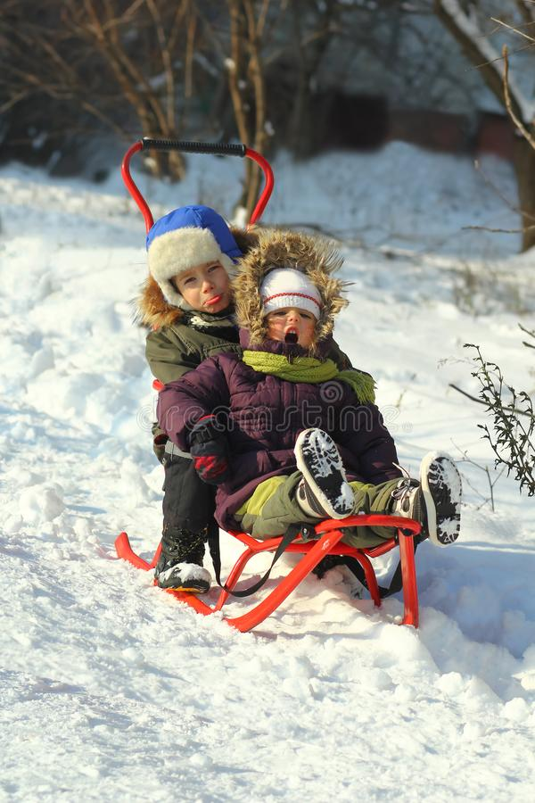 乘坐在倾斜下的滑稽的情感孩子在爬犁在一个晴朗的冬日 免版税库存图片