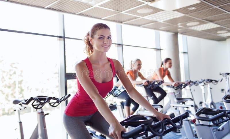 乘坐在健身房的锻炼脚踏车的小组妇女 库存照片