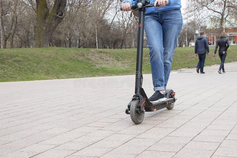在公园路上骑电动摩托车的女孩 技术生态友好型运输 现代 免版税库存图片