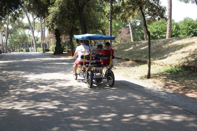 乘坐在别墅博尔盖塞,罗马的游人一辆人力车 库存图片