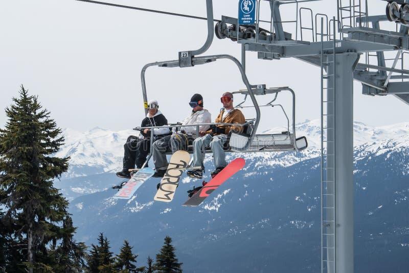 乘坐在吹口哨的滑雪电缆车,加拿大的滑雪者。 免版税库存图片