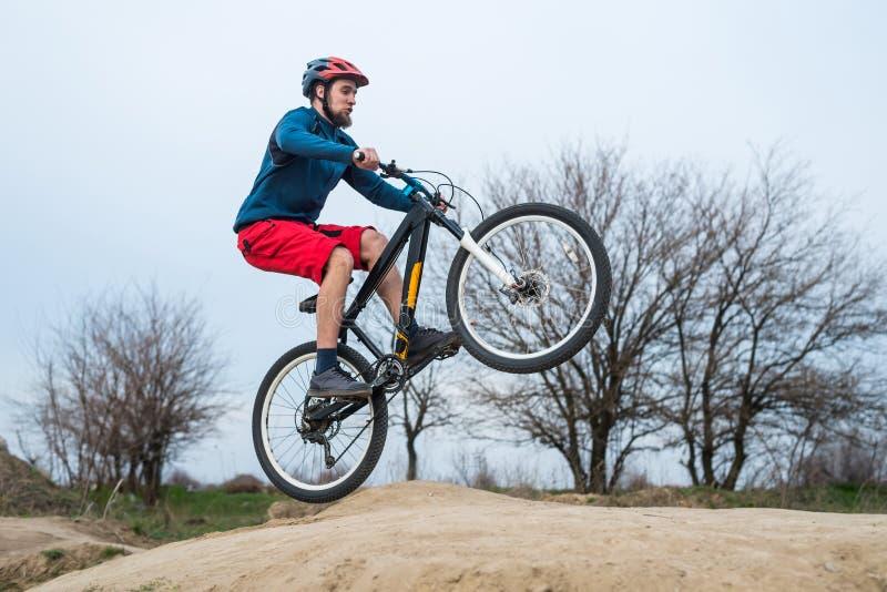 乘坐在土的蓝色毛线衣和红色短裤的年轻骑自行车者 库存照片