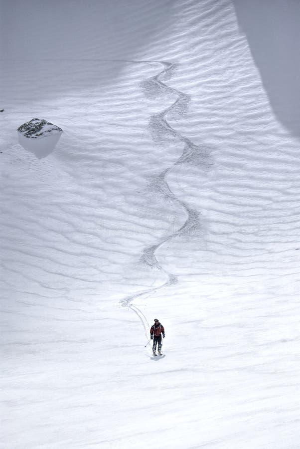 乘坐在小山下的男性滑雪者 免版税库存照片