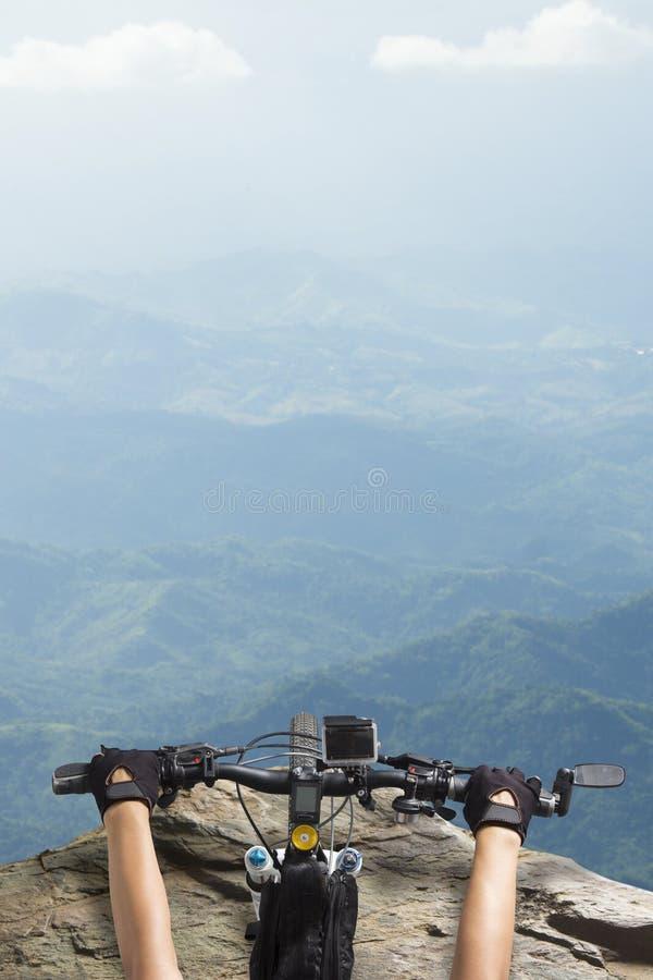 乘坐在山景的自行车把手上面的妇女 免版税库存图片