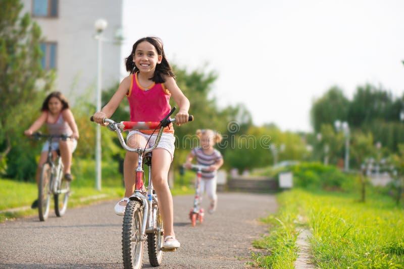 乘坐在自行车的三个愉快的孩子 免版税图库摄影