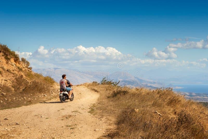 乘坐在自行车的游人在Pantokrator山山麓小丘  免版税库存图片