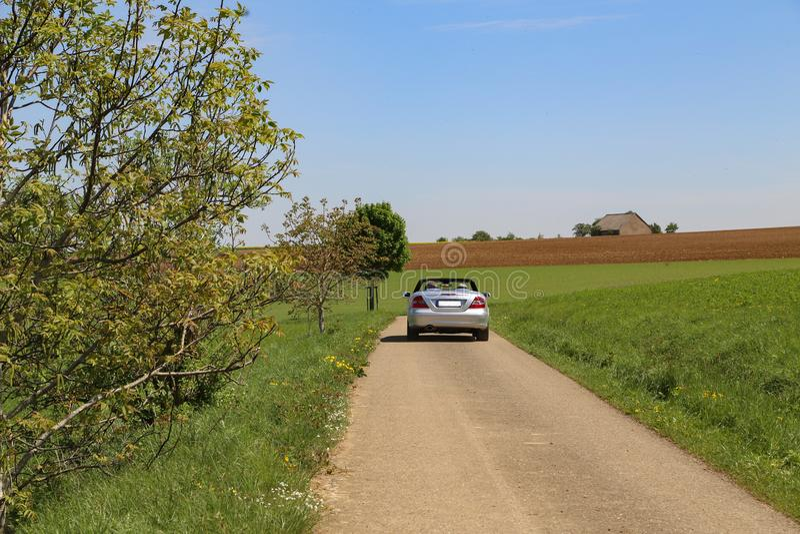 乘坐在领域中的一辆汽车 免版税库存图片