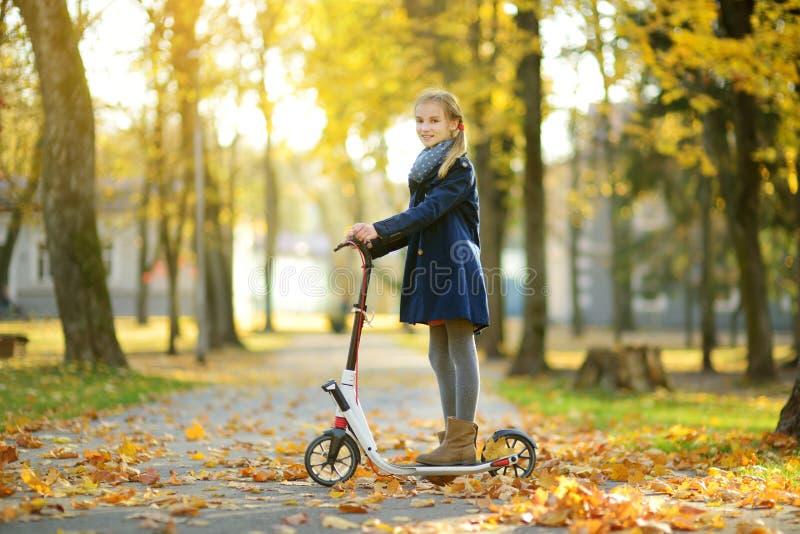 乘坐她的滑行车的可爱的少女在城市公园在晴朗的秋天晚上 乘坐路辗的俏丽的青春期前的孩子 库存图片