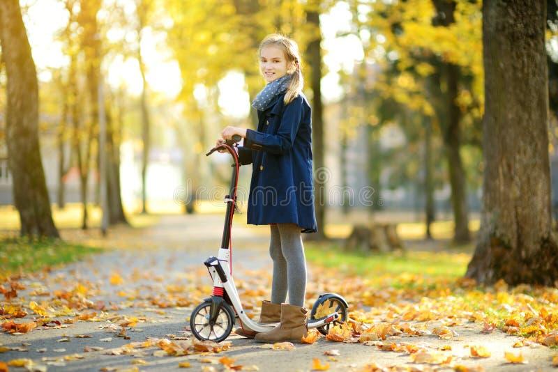 乘坐她的滑行车的可爱的少女在城市公园在晴朗的秋天晚上 乘坐路辗的俏丽的青春期前的孩子 免版税库存图片