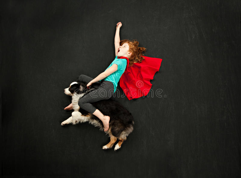 乘坐她的狗的超级英雄女孩 免版税库存照片