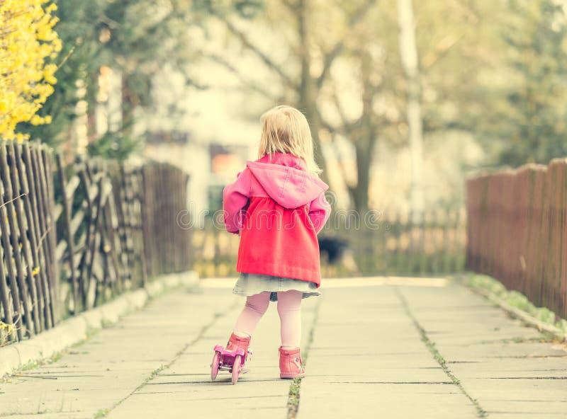 乘坐她的滑行车的岁女孩 免版税图库摄影