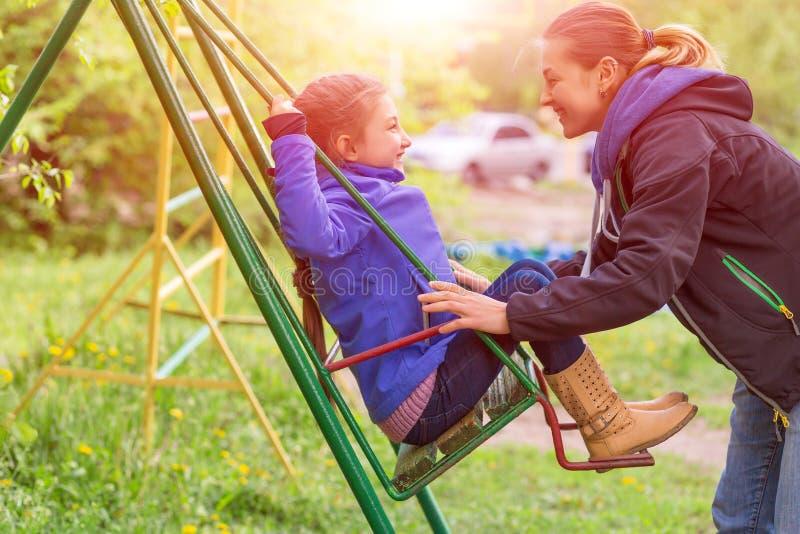 乘坐小女儿的年轻母亲在跷跷板在春天公园 库存照片