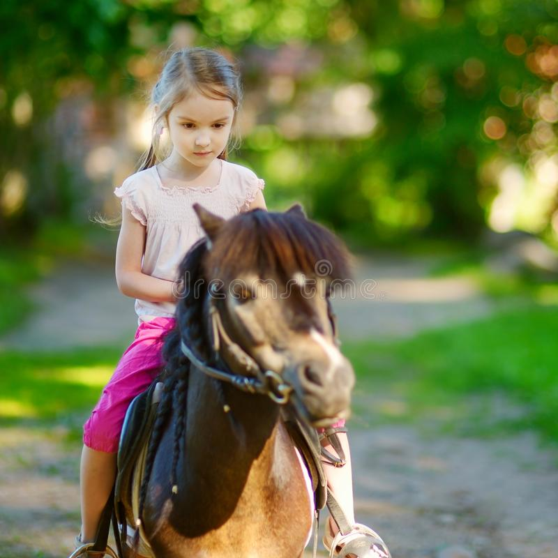乘坐小马的可爱的小女孩 库存图片