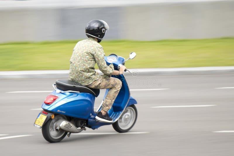 乘坐快速的蓝色滑行车的伪装衣裳的一年轻人  库存图片