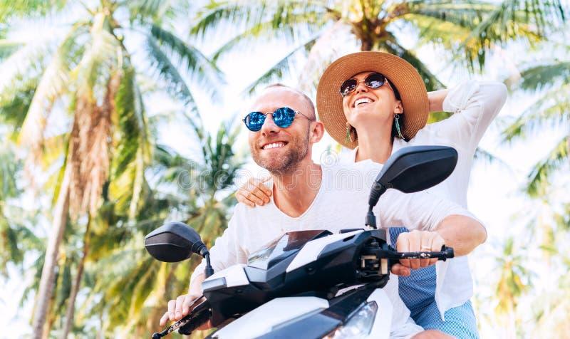 乘坐摩托车的愉快的微笑的夫妇旅客在他们的热带假期时在棕榈树下 免版税图库摄影