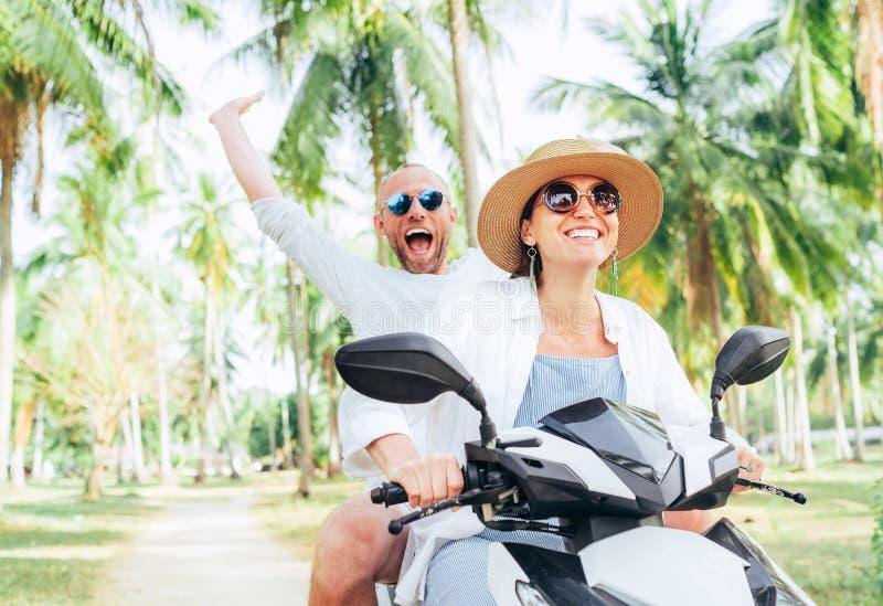 乘坐摩托车的笑的愉快的夫妇旅客在他们的热带假期时在棕榈树下 人情感地举了手  免版税图库摄影