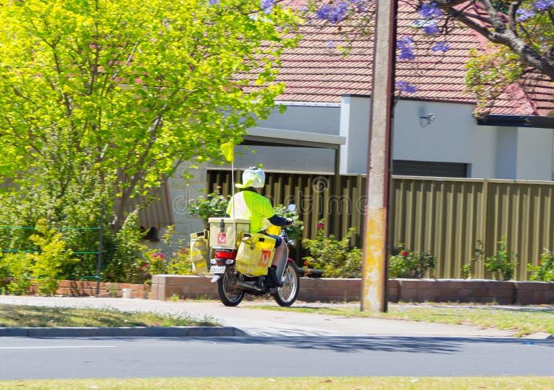 乘坐摩托车的Postie自行车澳大利亚邮差在上班时间 库存照片