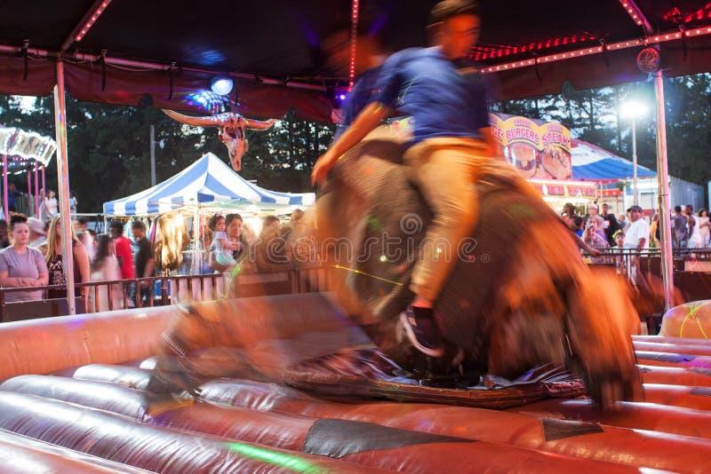 乘坐机械公牛的人行动迷离在集市 库存照片