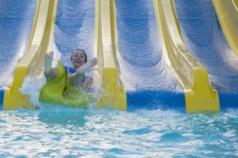 乘坐水滑道的美丽的女孩 去下来在橡胶环的愉快的妇女由橙色幻灯片在水色公园 夏天 库存照片