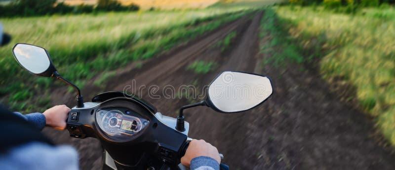乘坐沿一条空的路在森林里反对日落天空 滑行车方向盘和车速表特写镜头 fr的概念 免版税库存图片