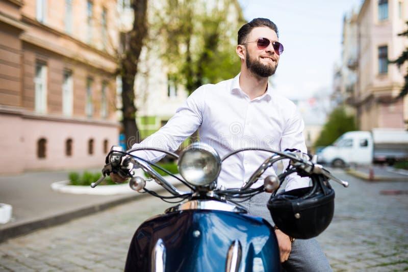 乘坐沿街道城市的太阳镜的年轻人滑行车 免版税库存照片