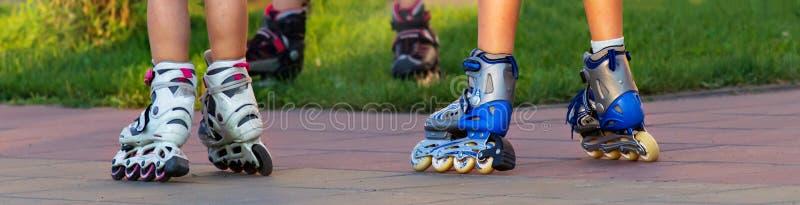 乘坐溜冰鞋的小孩子横幅在城市 关闭腿 免版税库存图片