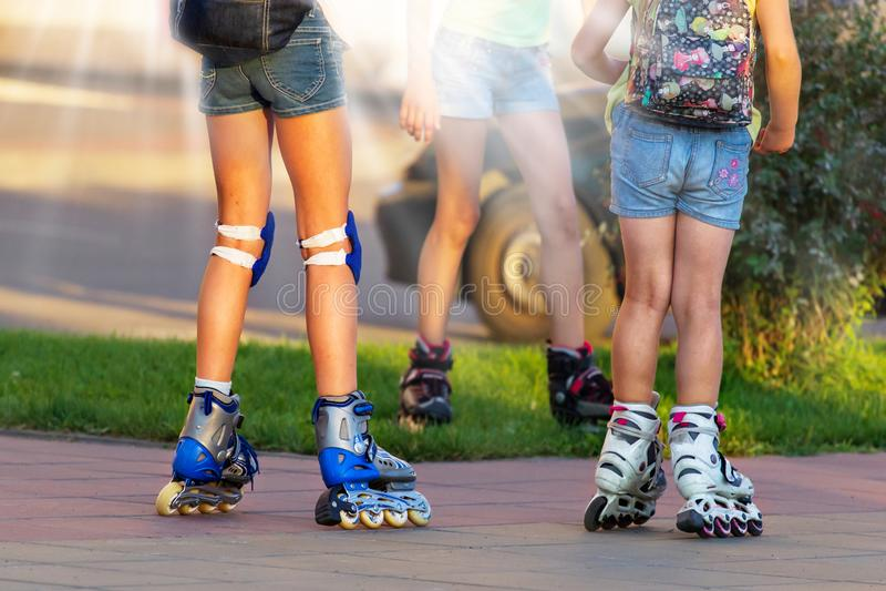 乘坐溜冰鞋的小孩子横幅在城市 关闭腿 库存照片