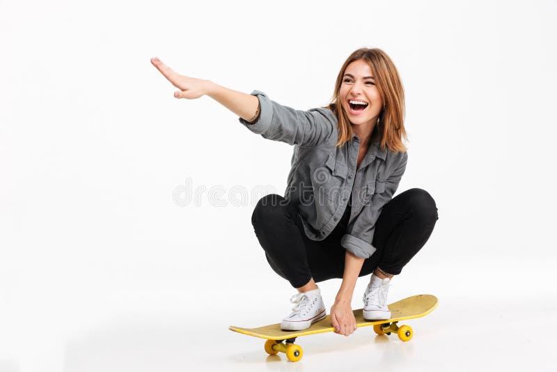 乘坐滑板的一个愉快的快乐的女孩的画象 免版税库存照片