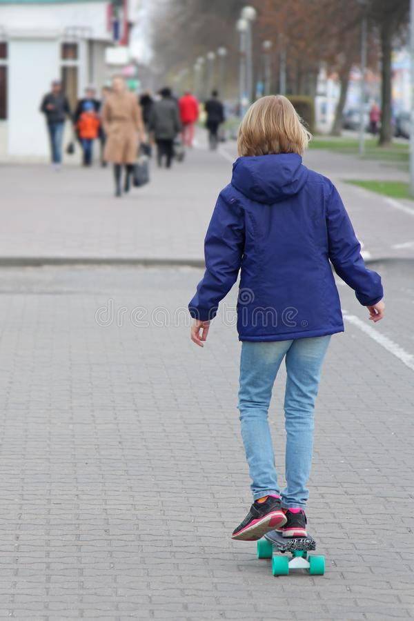 乘坐滑板的女孩在城市街道 青春期前的年龄的孩子在步行的 库存照片