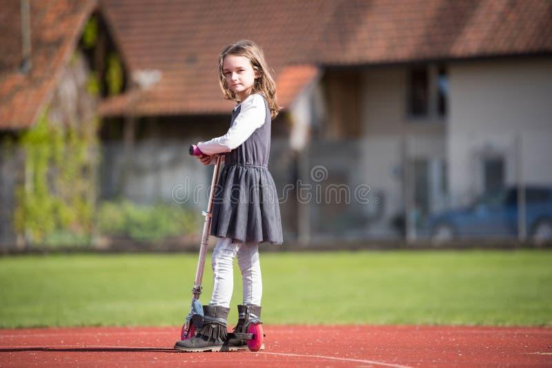 乘坐滑行车的小女孩在体育设施 库存照片