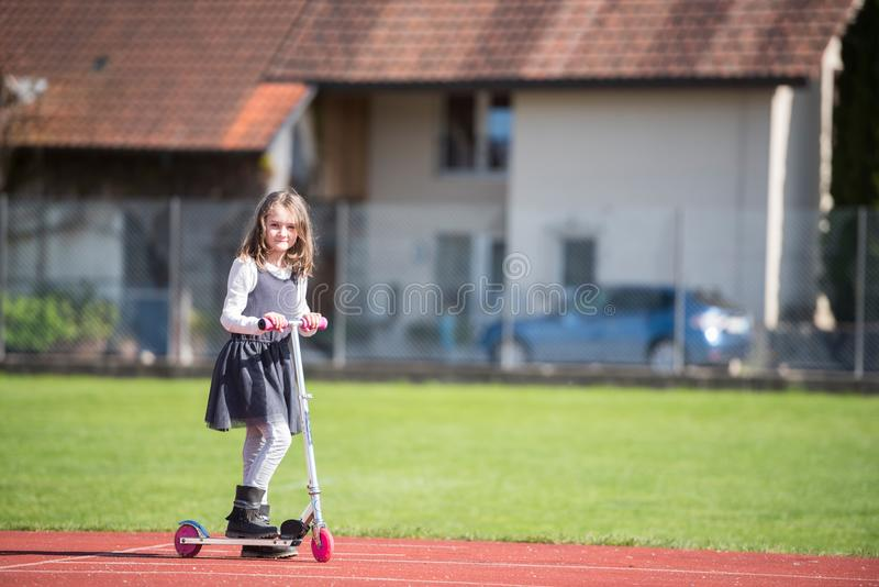 乘坐滑行车的小女孩在体育设施 免版税库存图片