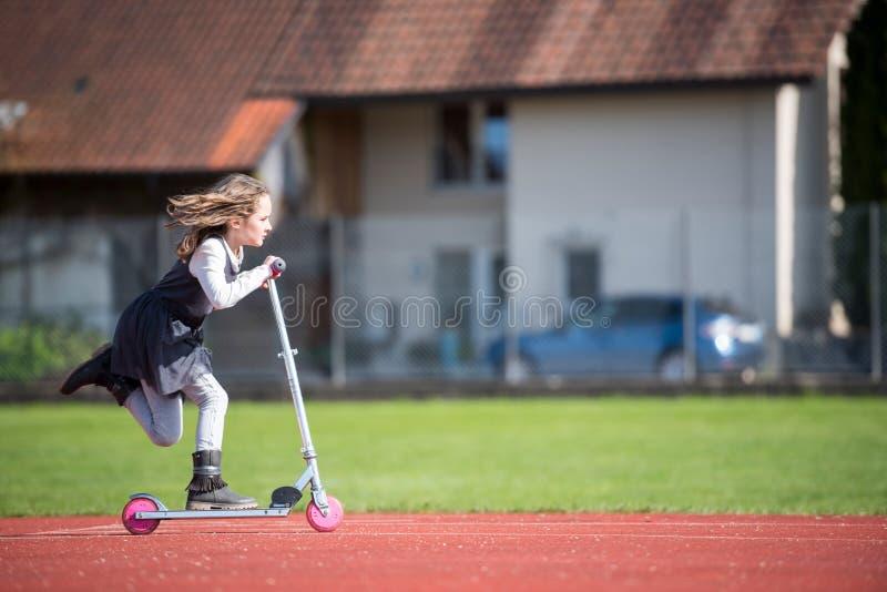 乘坐滑行车的小女孩在体育设施 免版税库存照片