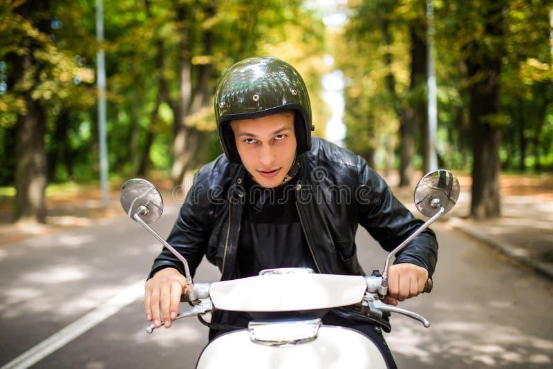 乘坐滑行车的英俊的人在城市街道在夏日 愉快的微笑的年轻男性特写镜头画象在葡萄酒滑行车的 免版税库存图片