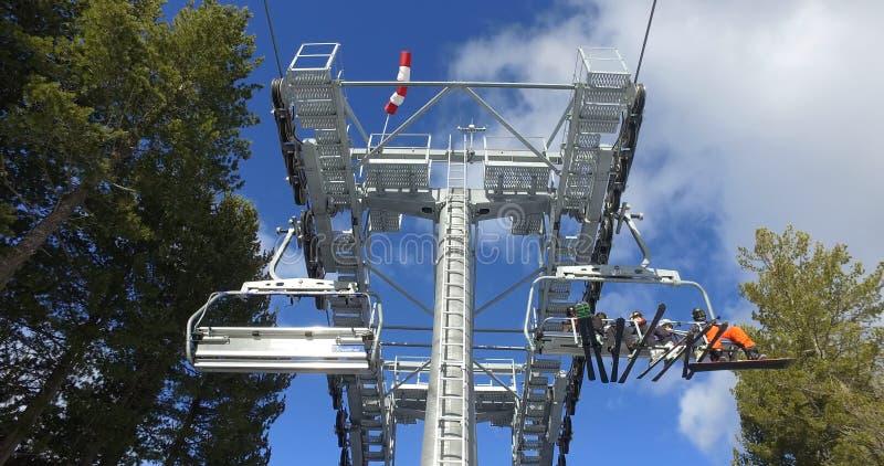乘坐滑雪电缆车的滑雪者和挡雪板,运输在山坡上面  库存照片