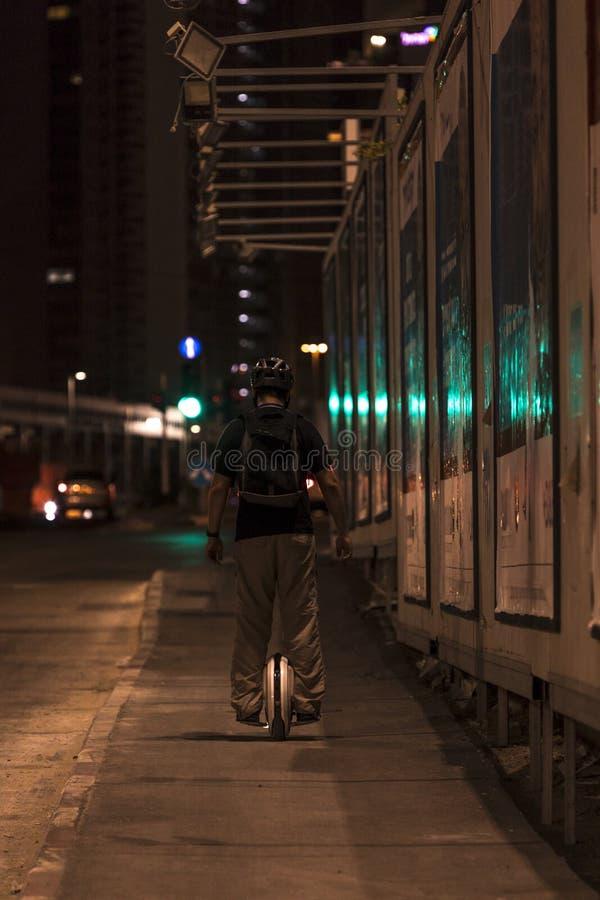 乘坐电单轮脚踏车的人在晚上 免版税库存图片