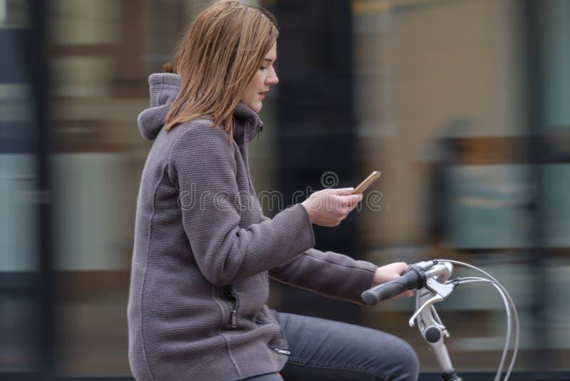 乘坐自行车和神色在她的智能手机,危险的女孩 免版税库存照片