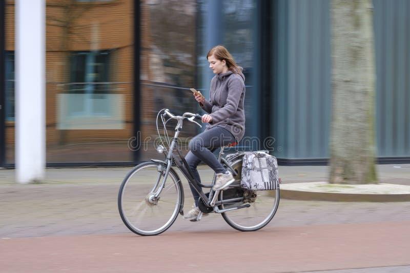 download 乘坐自行车和神色在她的智能手机,危险的女孩 库存照片.