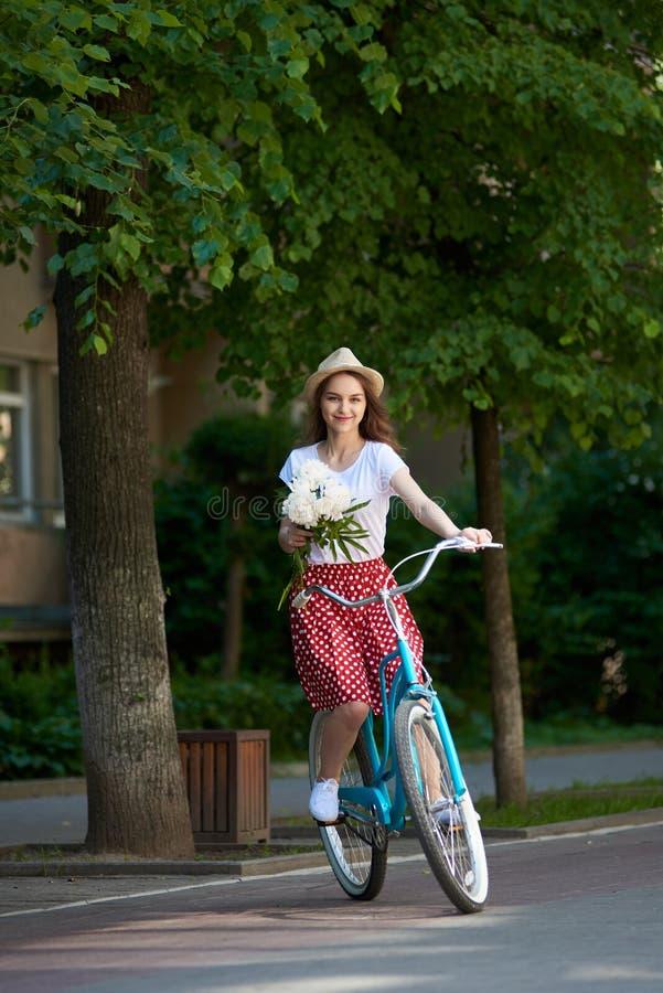 乘坐蓝色自行车下来被铺的城市街道的红色裙子的微笑的俏丽的女孩围拢与绿色树 库存照片