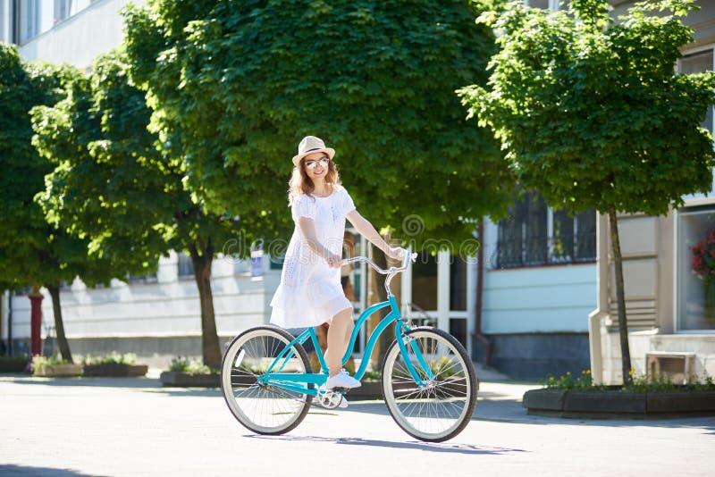 乘坐蓝色葡萄酒骑自行车和看对照相机的白色礼服的微笑的女孩 免版税库存图片
