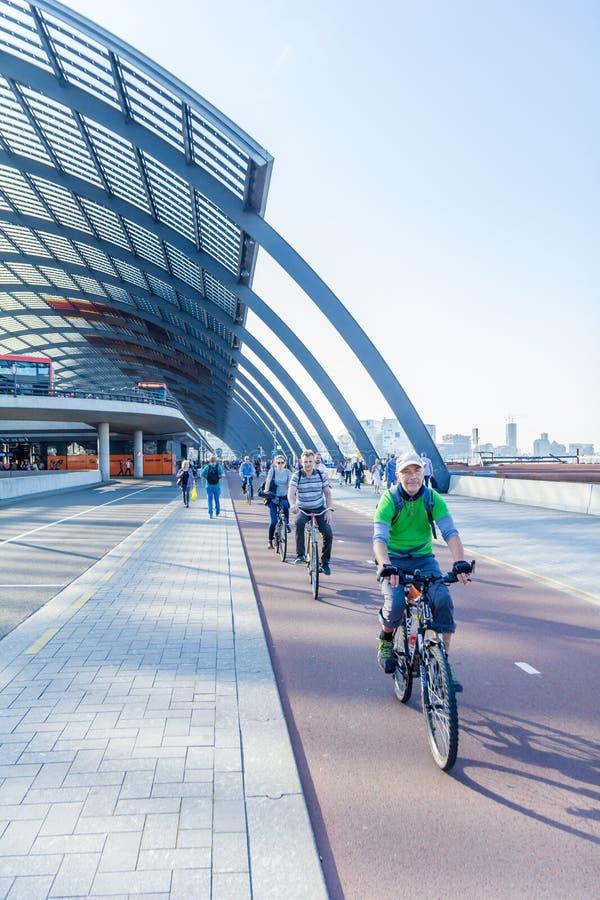 乘坐过去阿姆斯特丹中央驻地的骑自行车者 免版税图库摄影