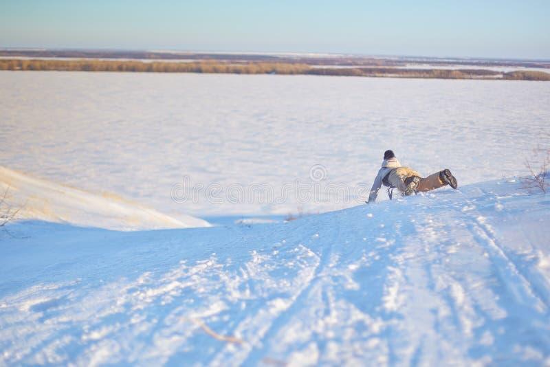 乘坐雪撬的快乐的女孩下坡在一个白色晴朗的冬天山风景的一串积雪的爬犁足迹 图库摄影